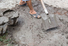 Worker stirs concrete shovel Stock Images