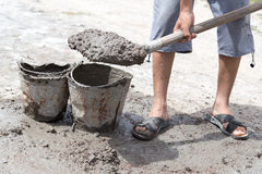 Worker stirs concrete shovel Royalty Free Stock Photo