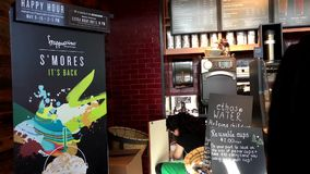 Worker stocking cups with happy hour sale sign. At Starbucks coffee shop stock footage
