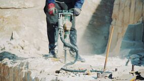A worker at a stone quarry drills a sandstone block with a jackhammer.