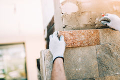 Worker with stone tiles in construction site. masonry details on exterior wall with trowel putty knifeworker installing sto. Worker installing stone tiles in Royalty Free Stock Photos