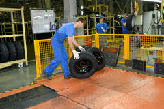 The worker stores automobile wheels in assembly shop. Automobile Royalty Free Stock Photo