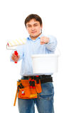 Worker stretching paint bucket and brush Royalty Free Stock Photography