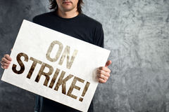 Worker on strike, man holding poster with printed protest messag Royalty Free Stock Photography