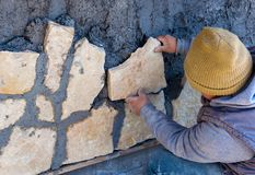Worker stuck stone cladding on the facade. Worker stuck stone cladding on the outside facade Royalty Free Stock Photo