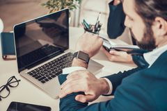 Worker looking at watch at desk in office. Worker in suit looking at watch at desk in office royalty free stock images