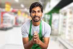 Worker at supermarket with joint hands. Indian worker man at supermarket or hypermarket with joint hands as begging gesture wearing green apron royalty free stock images