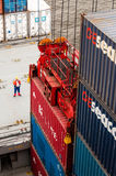 Worker supervising container uploading at dock of a container ship Royalty Free Stock Images