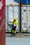 Worker supervising container uploading at dock Stock Image