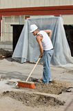 Worker Sweeping Dirt. Construction worker sweeping up dirt at construction site Stock Images