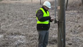Worker with tablet PC at the high-voltage pole in winter stock video