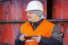 Worker with tablet PC near the red metal door Royalty Free Stock Photo