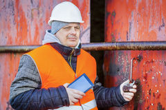 Worker with tablet PC near the red metal hangar door Stock Images
