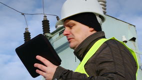 Worker with tablet PC near transformer stock video