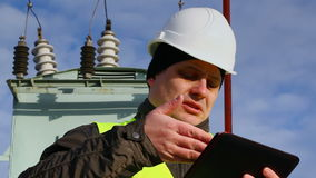 Worker with tablet PC near transformer stock video footage