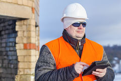 Worker with tablet PC near unfinished building Stock Photography