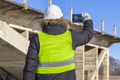 Worker take pictures on tablet near the unfinished bridge. In winter day stock photography