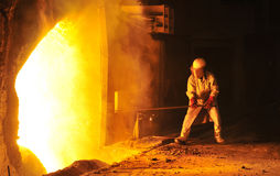 Worker takes a sample at steel company. Worker takes a sample inside of a steel company Royalty Free Stock Image
