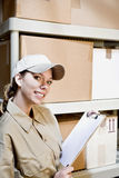 Worker taking inventory. Young woman in supply room taking inventory Stock Photo