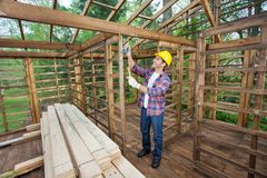 Worker Taking Measurements In Timber Cabin Stock Photography