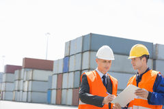 Worker taking sign of supervisor on clipboard in shipping yard Royalty Free Stock Image