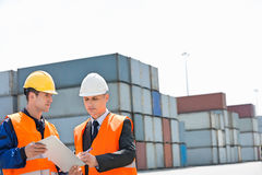 Worker taking sign of supervisor on clipboard in shipping yard stock photo