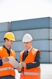 Worker taking sign of supervisor on clipboard in shipping yard Stock Photos