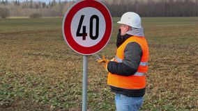 Worker talking on the cell phone near road sign stock footage