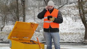 Worker talking on the cell phone near the sandbox in winter stock footage