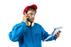 Worker talking on the phone. Worker who looks at a project and talking on the phone Royalty Free Stock Image