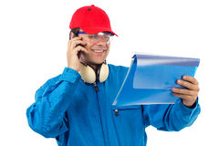 Worker talking on the phone. Worker who looks at a project and talking on the phone Royalty Free Stock Photo