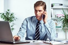 Worker talking on the phone and looks at the laptop. Photo of successful manager working with financial data in the office. Business concept Stock Photo