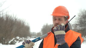 Worker talking on the radio, in the hands holding a sledgehammer stock footage