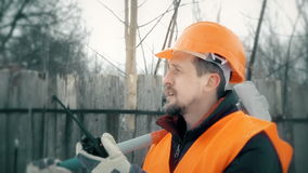Worker talking on the radio, in the hands holding a sledgehammer stock video footage