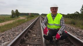 Worker talking and showing gestures on railway track. In summer day stock video footage