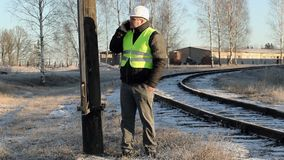 Worker talking on smartphone at the high-voltage pole near railway in winter stock footage