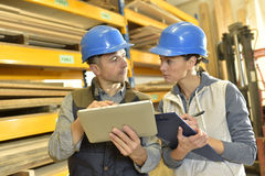 Worker talking to overseer in warehouse Royalty Free Stock Image