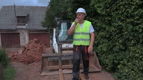 Worker talking on walkie talkie near tractor stock footage