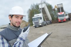 Worker talking on walkie talkie on quarry site stock image