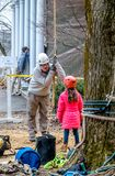 Worker talks to scared child. March 17, 2019 New Carlisle Indiana USA; a tree worker during an event at the St Joseph county parks, reassures a scared child stock image