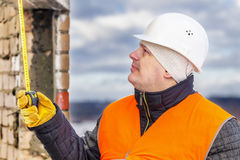 Worker with tape measure near the building Royalty Free Stock Image