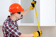 Worker with a tape measure. Worker in a red protective helmet with a tape measure Stock Photography