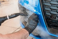 Worker with tattoos is warming up the paint protection film to make the installation easier. Paint protection isis a thermoplastic urethane often self healing royalty free stock photo