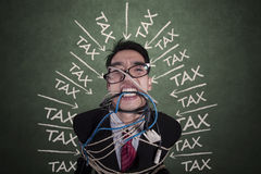 Worker with tax pressure bound by rope Royalty Free Stock Images