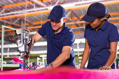 Worker teaching employee. Senior textile worker teaching new employee about cutting material Royalty Free Stock Photography