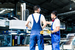 Worker team in factory discussing in front of machine Stock Photos