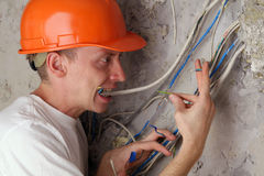 Worker teeth compresses dangling wires Stock Image