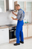 Worker Testing Kitchen Hood With Multimeter. Male Worker In Overall Testing Kitchen Hood With Multimeter In Hands royalty free stock image