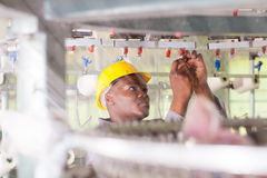 Worker in textile factory. African american blue collar worker working in textile factory Stock Images