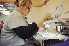 Worker in textile industry sewing royalty free stock image